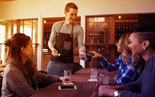 cameriere che usa un dispositivo wireless per accettare un pagamento tramite carta di credito al tavolo